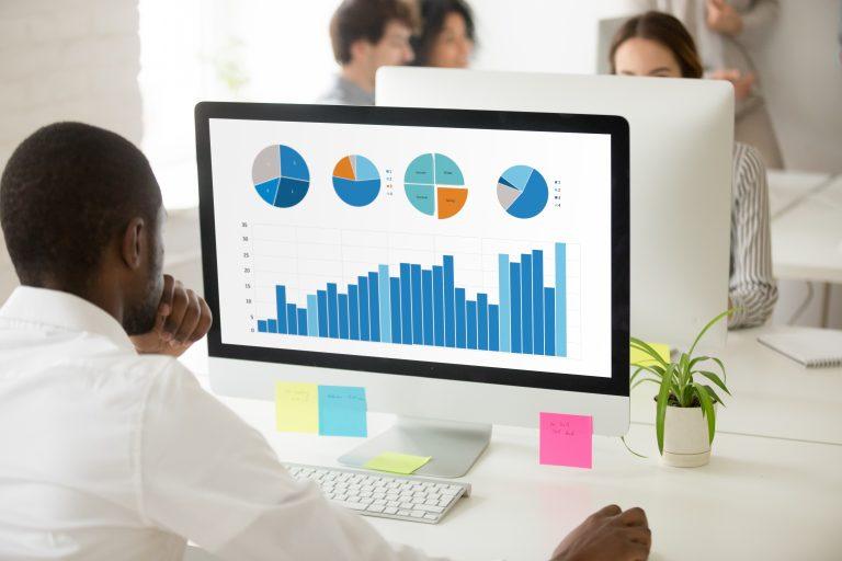 Man checking healthcare analytics dashboard on his computer.